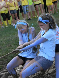 Two students participating in a game of tug-of-war during orientation