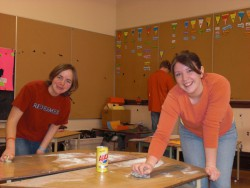 Two female students cleaning a classroom