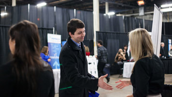 A male student shaking hands with a potential employer at a job fair